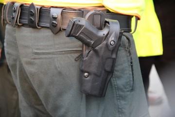 Detailaufnahme einer Waffe, die eim Polizist am Gürtel im Halfter trägt.
