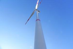 Aus der Froschperspektive fotografiertes Windrad vor blauem Himmel.