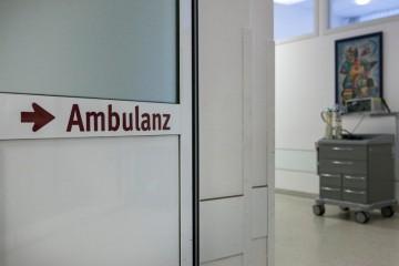 """Blick durch eine offene Glastür im Krankenhaus, auf der Tür der Schriftzug """"Ambulanz""""."""