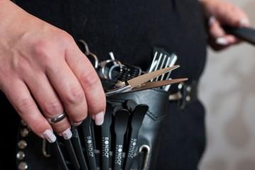 """Nahaufnahme einer Friseurin, die eine Gürteltasche trägt, die mit verschiedenen Scheren, Kämmen und anderem """"Werkzeug"""" bestückt ist."""