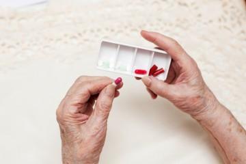 Zwei alte Hände vor einer Spitzentischdecke - in der rechten Hand eine Dose mit vorsortierten Medikamenten, in der linken Hand eine der Tabletten.