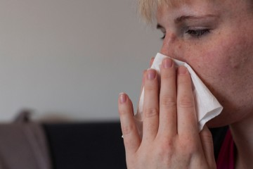 Eine junge Frau putzt sich mit einem Papiertaschentuch die Nase.