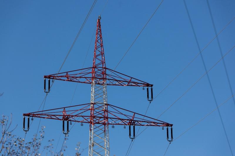 Aufnahme des oberen Teils eines rot-weißen Hochspannungsmastes vor blauem Himmel.