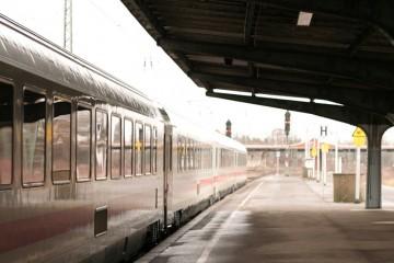 Blick vom überdachten Teil eines Bahnsteiges auf einen wartenden Zug.