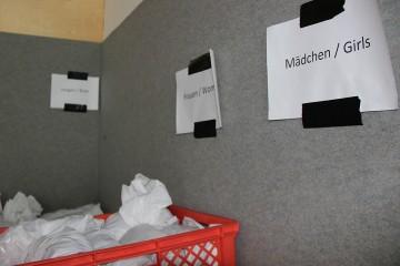 An eine graue Teppichwand geklebte Zettel in einer Flüchtlingsunterkunft