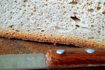 Nahaufnahme eines hellen Broten, das aufgeschnitten auf einem Holzteller liegt, das Brotmesser mit hölzernem Griff liegt davor