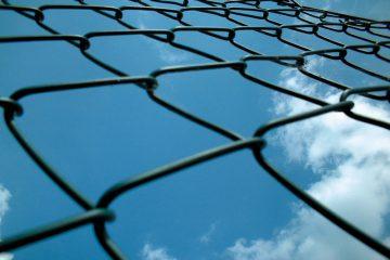 Blick aus der Froschperspektive an einem Maschendrahtzaun hoch, im Hintergrund blauer Himmel und weiße Wolken