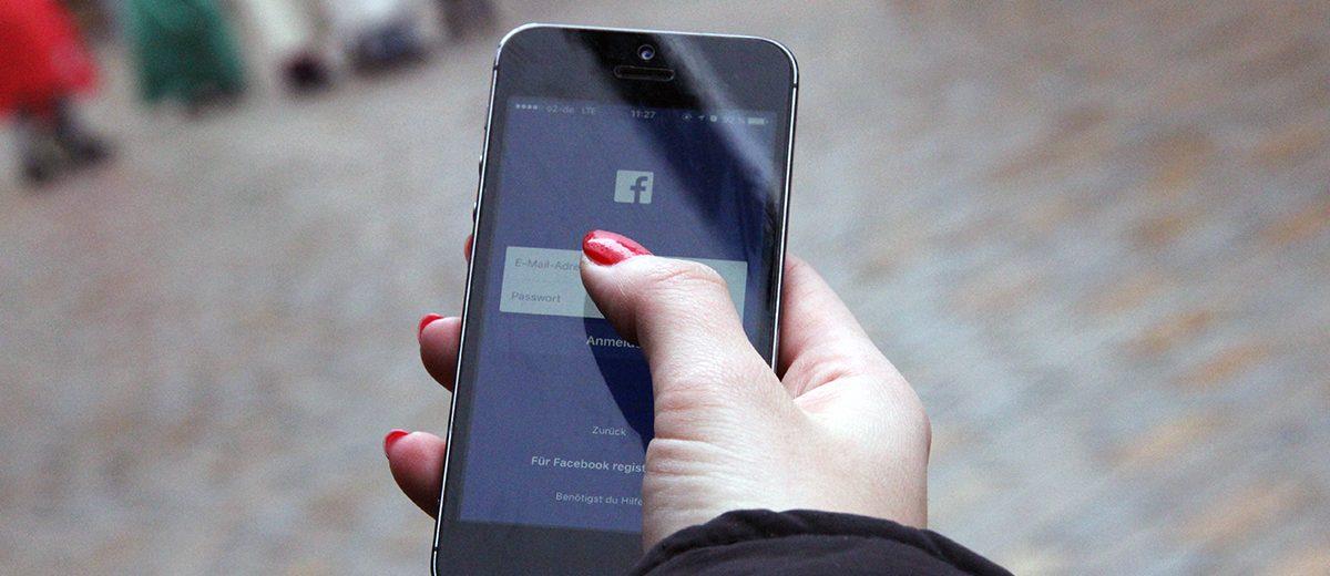 Blick auf ein von einer Frau bedientes Smartphone, auf dessen Bildschirm die Facebook-App geöffnet wird