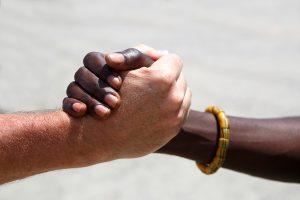 Nahaufnahmer zweier Hände - die eine weiß, die andere schwarz - die sich festhalten.