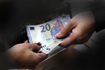 Nahaufnahme vor düsterem Hintergrund von zwei Händen, die eine überreicht einige Geldscheine an die andere