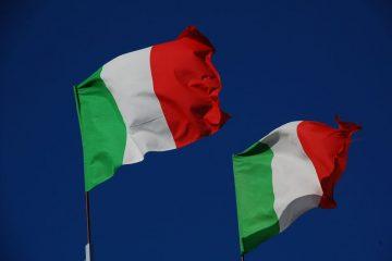 Zwei italienische Flaggen wehen vor tiefblauem Hintergrund