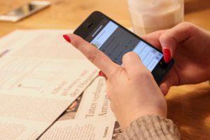 Eine Frau mit rot lackierten Fingernägeln tippt auf ihrem Smartphone eine Nachricht