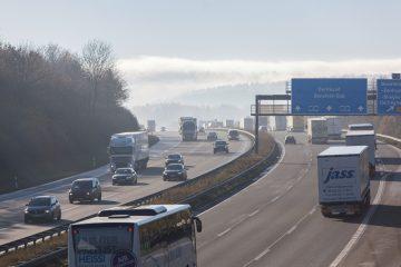 Blick von oberhalb auf eine dreispurige deutsche Autobahn, auf der mehrere Fahrzeuge unterwegs sind.