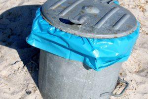 Nahaufnahme eines Blechmülleimers mit Deckel, unter dem eine blaue Mülltüte hervorragt.