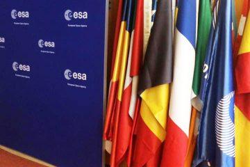 Verschiedene europäische Landerflaggen sowie eine Falle der eruopäischen Weltraumbehörde ESA, die neben einer dunkelblauen, mit dem ESA-Logo versehenen Wand aufgestellt wurden