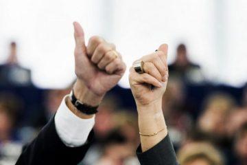 Nahaufnahme einer weiblichen und einer männlichen Hand, die mit dem Daumen nach oben zeigend im Parlament zur Abstimmung in die hochgehalten werden