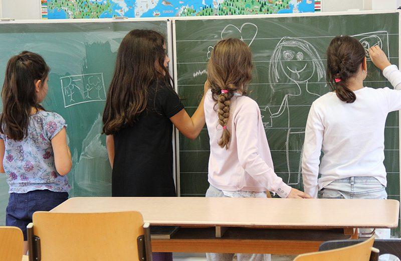 Vier Mädchen stehen an einer Tafel im Klassenzimmer und beschreiben und bemalen diese.
